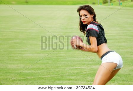 Beautiful young woman wearing American football top holding ball