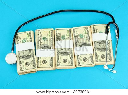 Healthcare cost concept: stethoscope and dollars on blue background