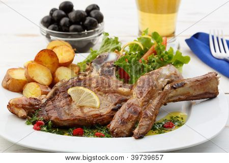 beef chops with potatoes and salad on a wood table