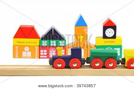 Wooden Train On The Railroad And Toy Houses Over White