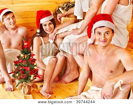 Group people in Santa hat  relaxing at sauna.