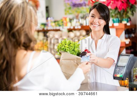 Shopping woman at the checkout paying by card