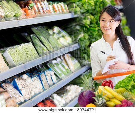 Woman at the supermarket with a shopping list