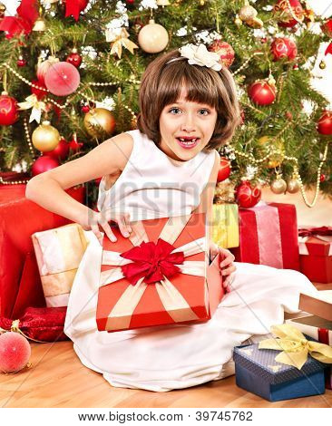 Happy child with gift box near Christmas tree.