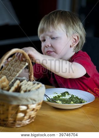 Child Eating Spinach Soup And Crispbread