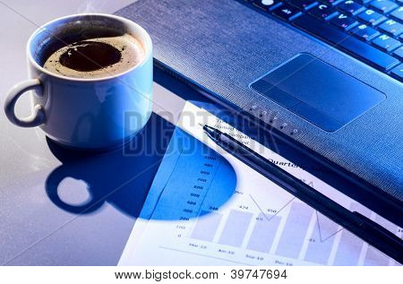 working at night, laptop and cup of hot evaporating coffee on table
