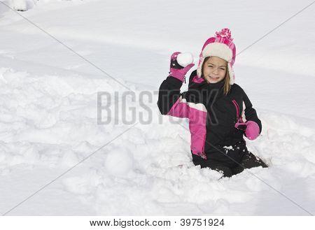 Little girl having a snowball fight