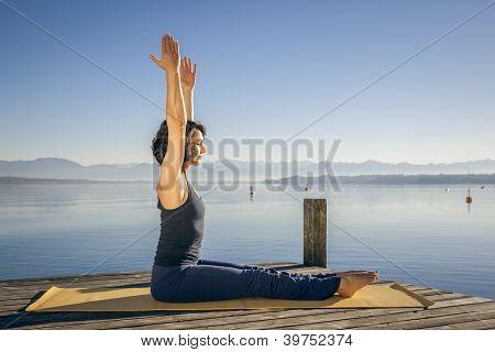 Ein Bild einer hübschen Frau tun Yoga am See