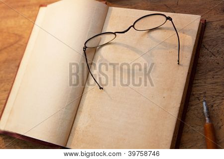 Blank inner title page of an 19th century book, with vintage glasses on top. Focus is in the area where title would be inserted (middle of the page below the glasses.)