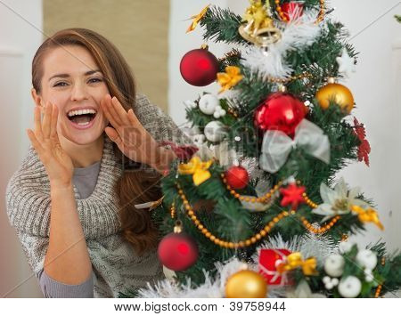 Happy Woman Shouting Through Megaphone Shaped Hands Out From Christmas Tree