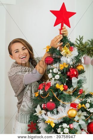 Happy Young Woman Hanging Christmas Top On Christmas Tree