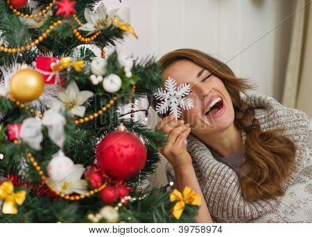 Happy Woman Sitting Playing With Christmas Tree Decoration