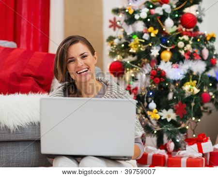 Smiling Young Woman With Laptop Sitting Near Christmas Tree