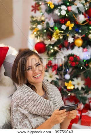 Happy Young Woman Writing Sms Near Christmas Tree