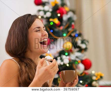 Smiling Young Woman In Pajamas Eating Cookies With Hot Chocolate