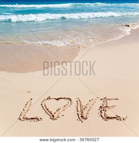 On sand at ocean edge it is written LOVE