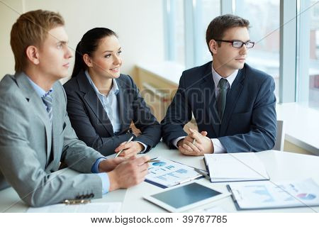 Image of three business people looking in the window at meeting