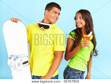 Portrait of happy couple with cocktail and skateboard looking at one another