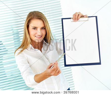 Portrait of young businesswoman pointing at clipboard and looking at camera
