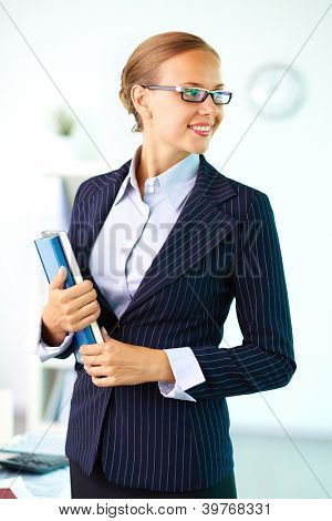 Portrait of elegant businesswoman with handbooks looking aside