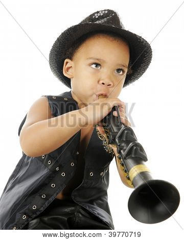 A biracial preschooler playing a clarinet in a sparkly black fedora and black leather vest.  On a white background.