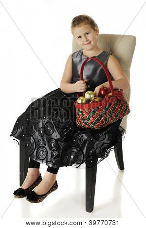 A happy elementary girl sitting in a dressy black dress while holding a red and green basket filled with ornaments.  On a white background.