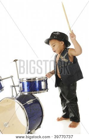 An adorable, barefoot preschooler dressed as a rock star with a drum stick poised high over a drum set, ready to
