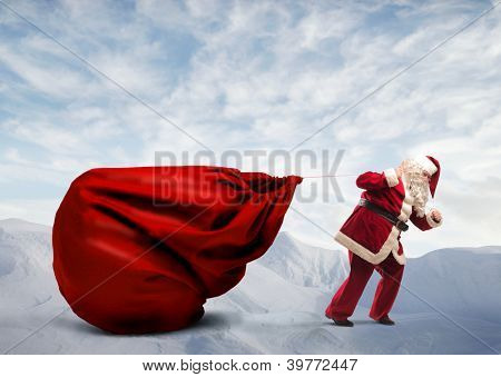 Santa Claus dragging his very large full of presents on a mountain