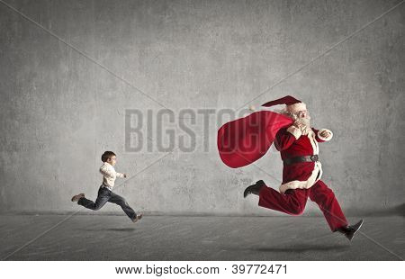 Santa Claus with his bag full of gifts runs away from a child who chases