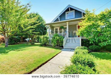 Cinzento pequeno velho americano frente Exterior casa com escadaria branca.