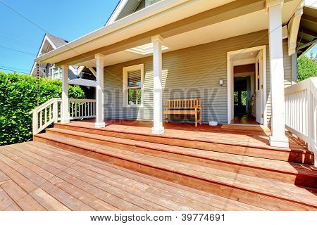 Back Porch Of Small Grey House With Bench