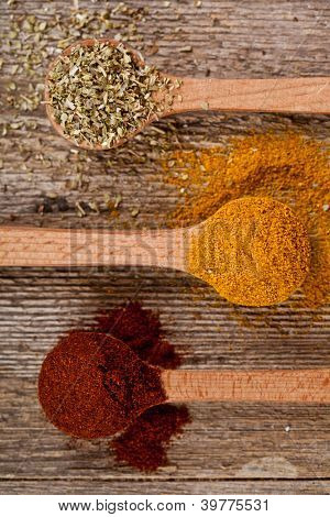 three spices in wooden spoons on rustic wooden background