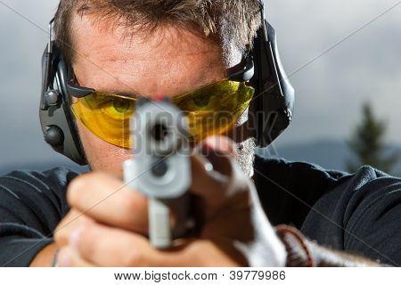 Man shooting on an outdoor shooting range, selective focus