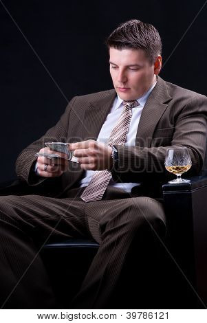 Businessman with drinks, cigars and money count