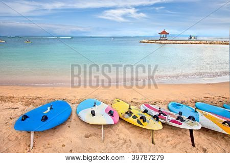 Surf boards on idyllic tropical sand Nusa Dua beach, Bali, Indonesia.