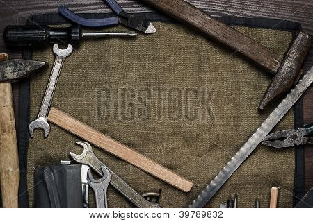 Old Rusty Construction Instruments Over Wooden Background