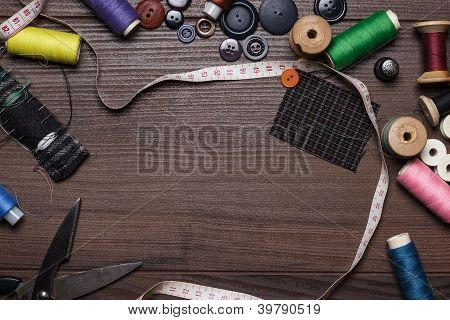 Threads Buttons And Needles Over Brown Wooden Table
