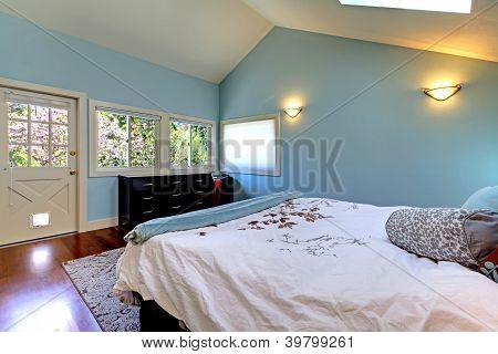 Blaues Schlafzimmer mit Bett und Oberlicht.