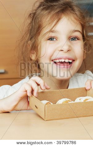 Smiling little girl holds open box of corrugated cardboard with cookies with almonds and icing sugar