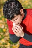 pic of snot  - Sick male athlete coughing and blowing her nose with a tissue beacuse autumnal illness - JPG