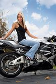 stock photo of crotch-rocket  - A pretty blonde woman seated on a motorcycle outdoors - JPG