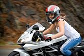 stock photo of bombshell  - A pretty blonde girl in action driving a motorcycle at highway speeds - JPG