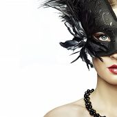 stock photo of masquerade  - Beautiful young woman in black mysterious venetian mask - JPG