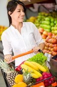 stock photo of local shop  - Female customer at the supermarket with a shopping cart - JPG