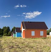 pic of hayfield  - Four bright multicoloured houses in the hayfield - JPG
