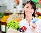 stock photo of local shop  - Shopping woman with a credit card looking happy - JPG