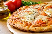 stock photo of crust  - A freshly baked traditional Pizza Margherita with tomatoes - JPG