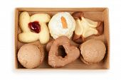 Several kinds of cookies and cakes in open box of corrugated cardboard