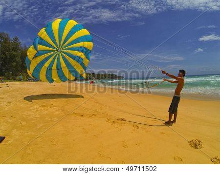PHUKET Tailândia 6 de agosto: Homem não identificado prepara um pára-quedas para os turistas na praia, em agosto