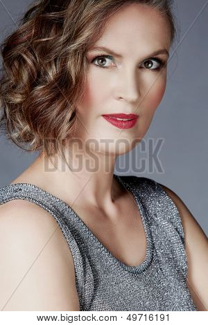 beautiful fourty year old woman with fashion makeup, curly hairstyle on grey blue studio background. Wearing silver top
